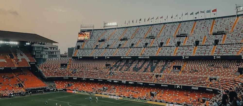 people watching football game during daytime
