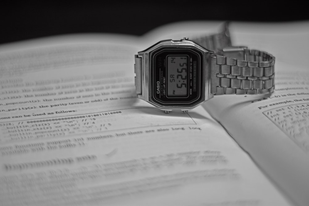 silver casio digital watch at 11 00