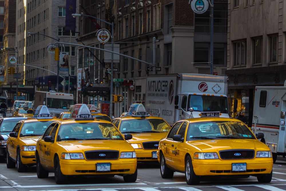 yellow taxi cab on road near white concrete building during daytime