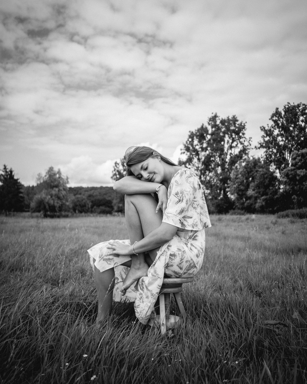woman in white dress sitting on grass field
