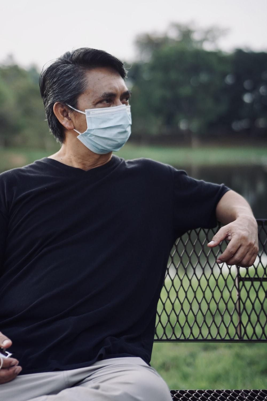 man in black crew neck shirt wearing white face mask