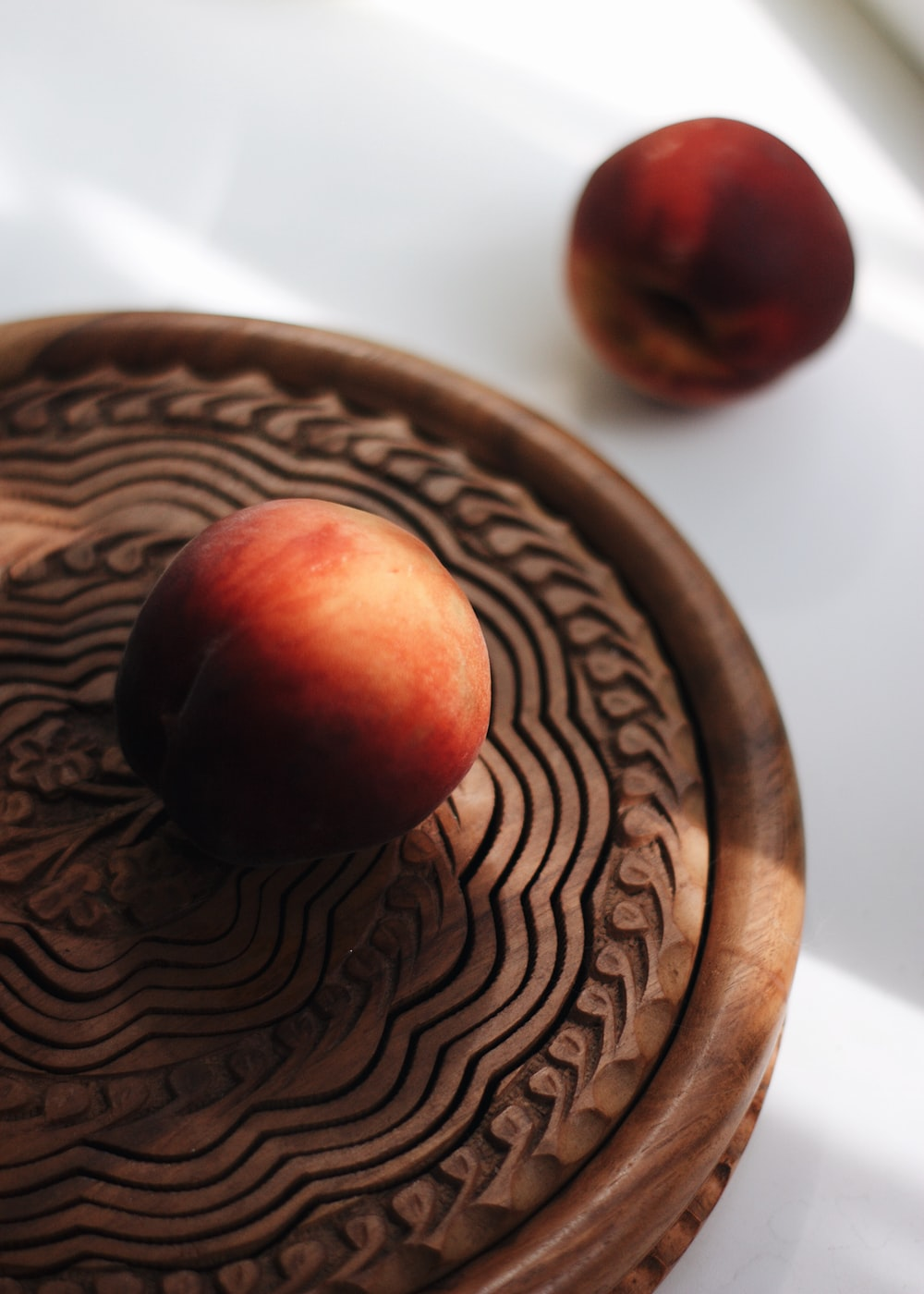 red apple fruit on brown wooden round table