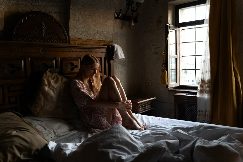 woman in white floral dress lying on bed