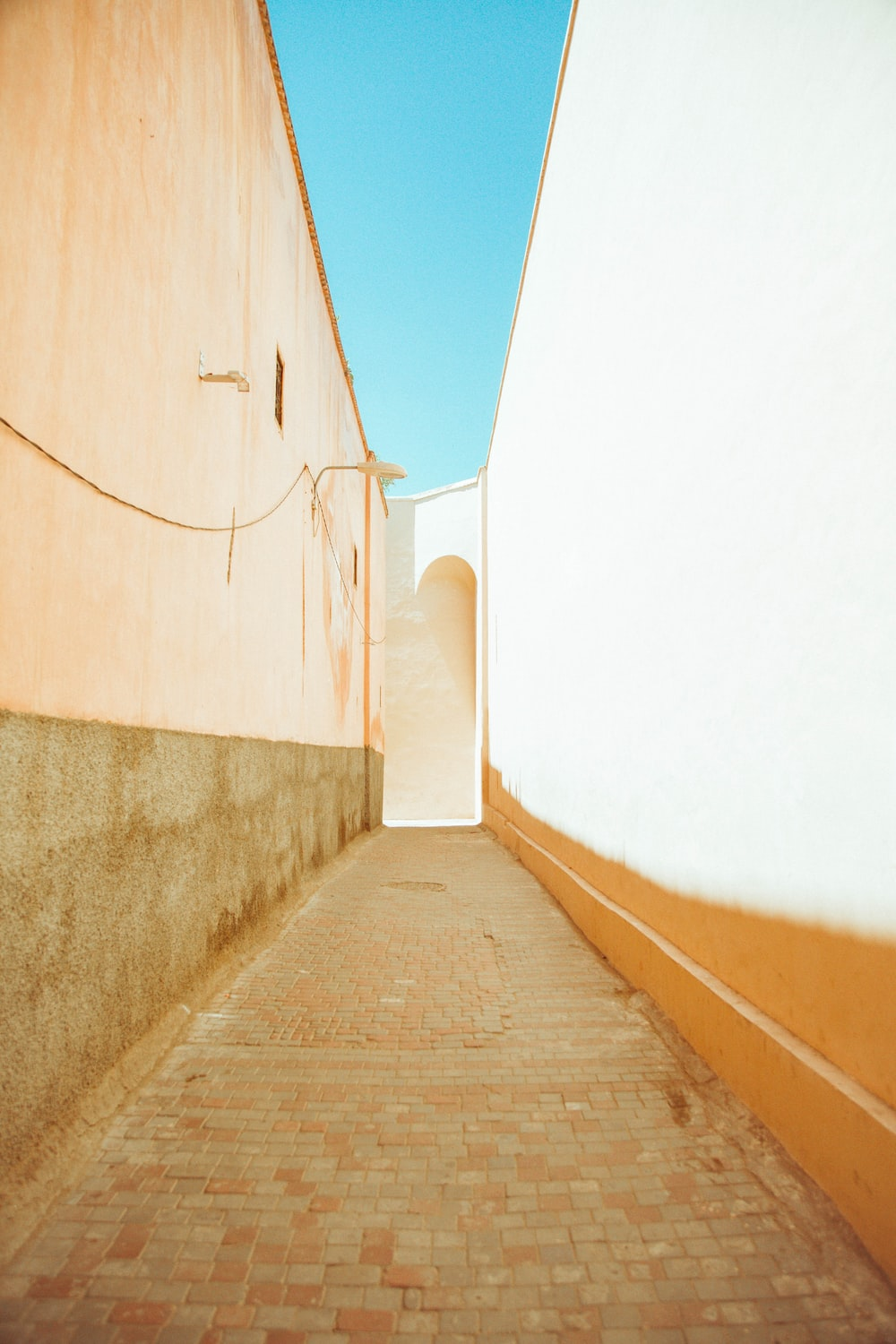 brown wooden pathway between white wall