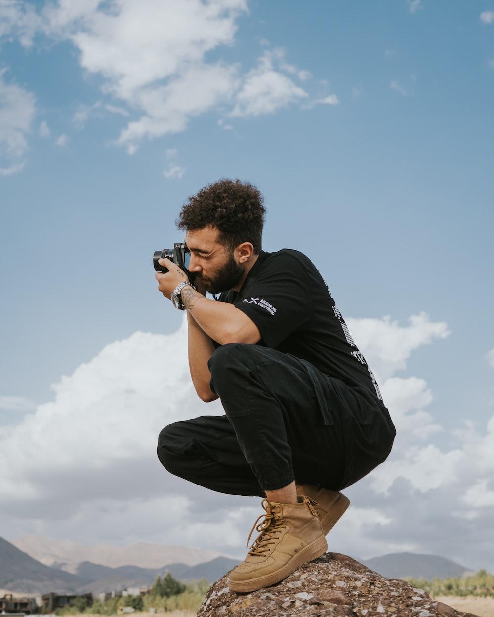 man in black shirt and brown pants holding black dslr camera