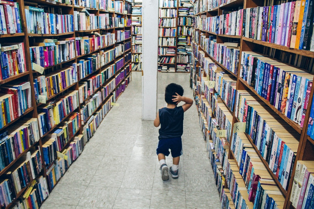 boy in black t-shirt and white shorts standing in front of books on shelves
