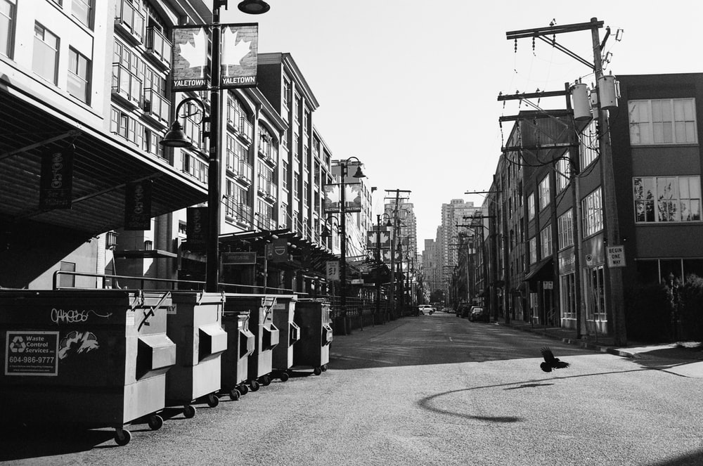 grayscale photo of street with cars parked beside buildings
