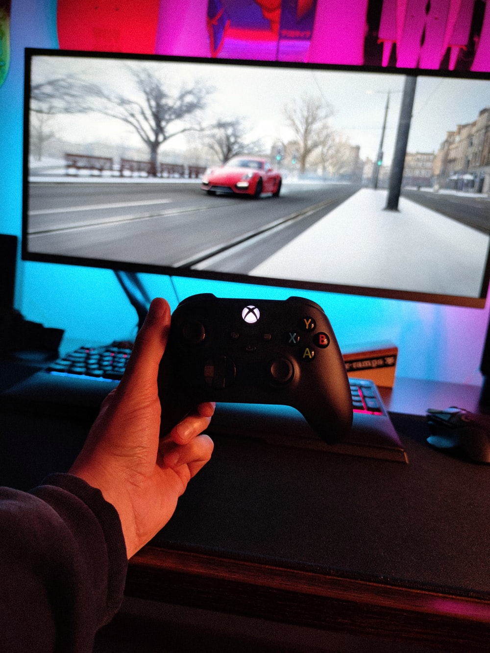 person holding black xbox one game controller