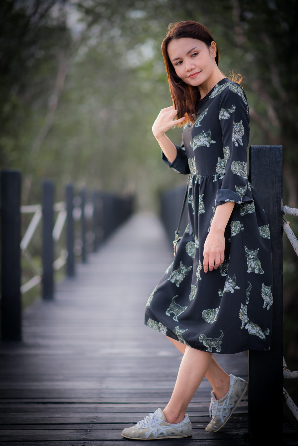 woman in black and white floral dress standing on gray concrete pathway during daytime