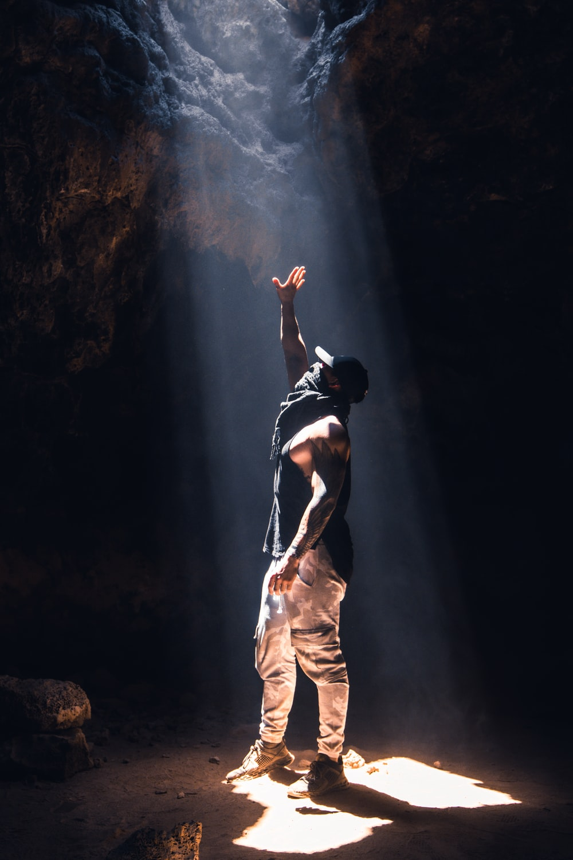 man in black tank top and beige pants standing on rock