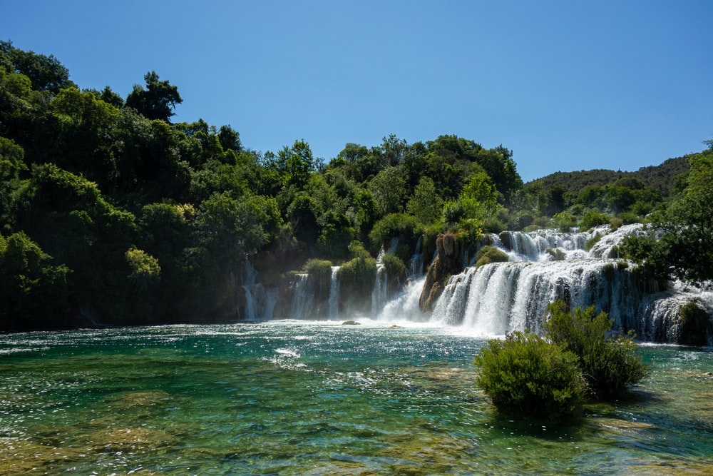 waterfalls near green trees under blue sky during daytime