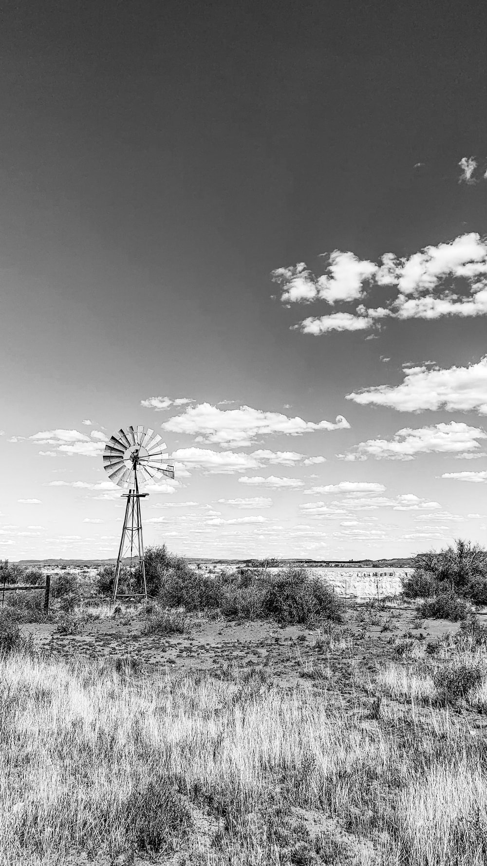 grayscale photo of windmill under cloudy sky
