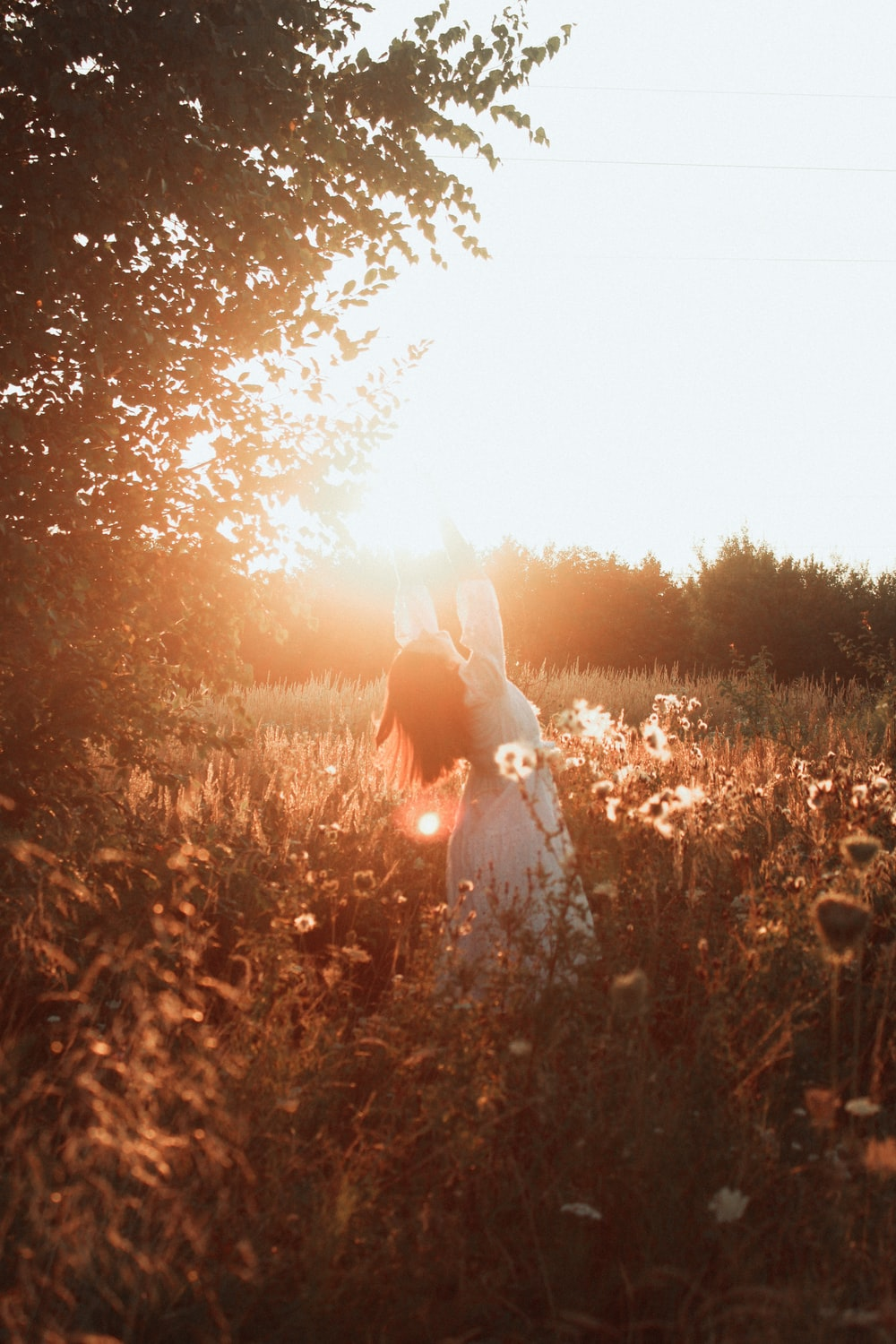 woman in white dress standing on brown grass field during sunset