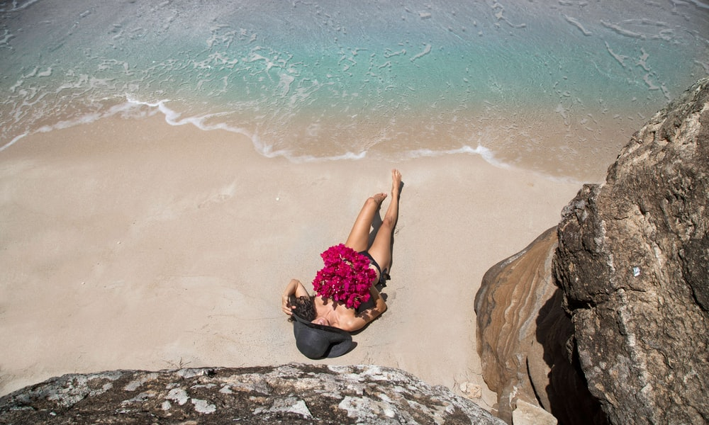 woman in black and pink floral dress sitting on brown rock near body of water during