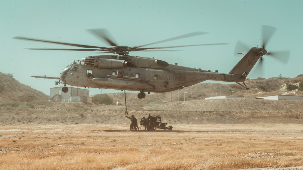 gray helicopter on brown field during daytime