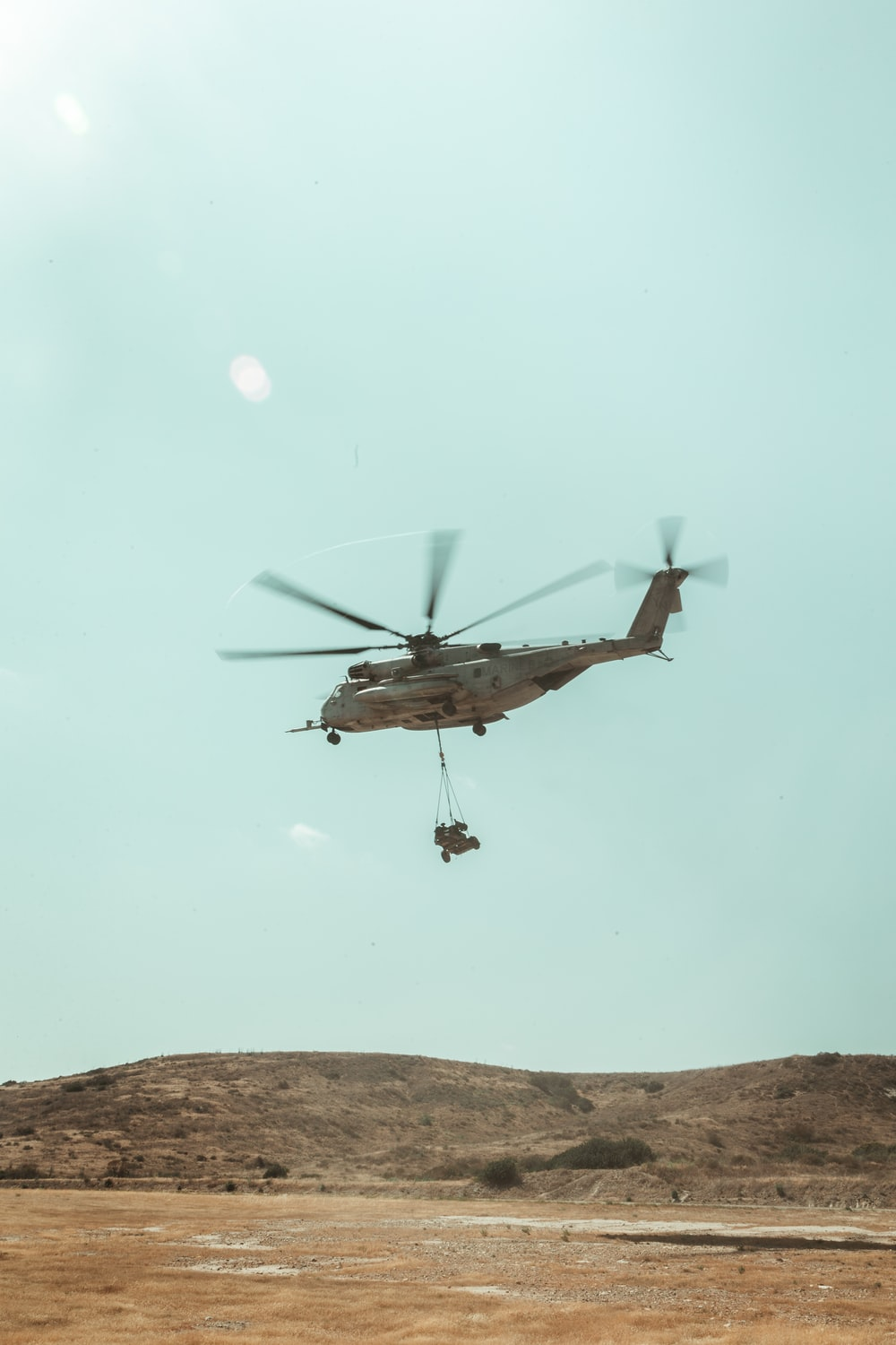 brown and white helicopter flying during daytime