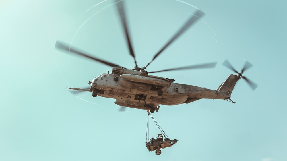 brown helicopter flying in the sky