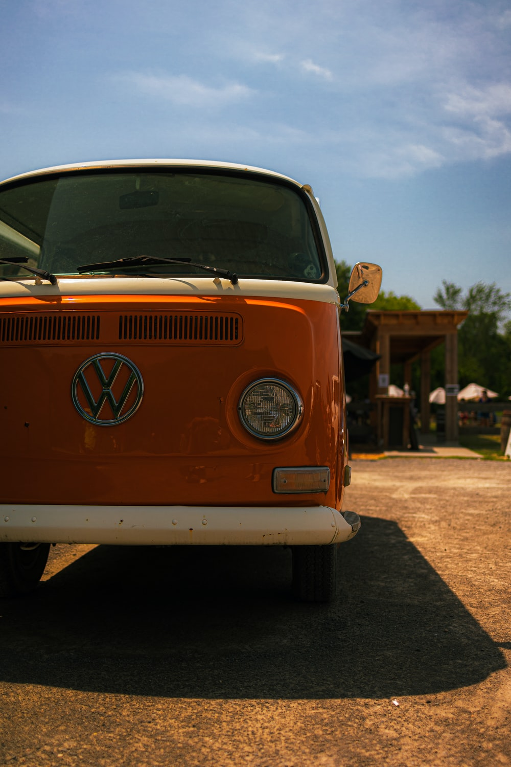 orange and white volkswagen t-2 parked on brown dirt road during daytime