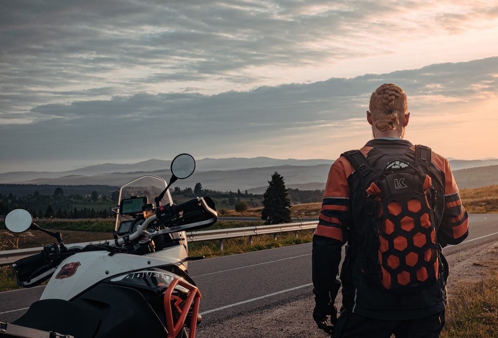 man in black and orange jacket standing beside red and black motorcycle during daytime