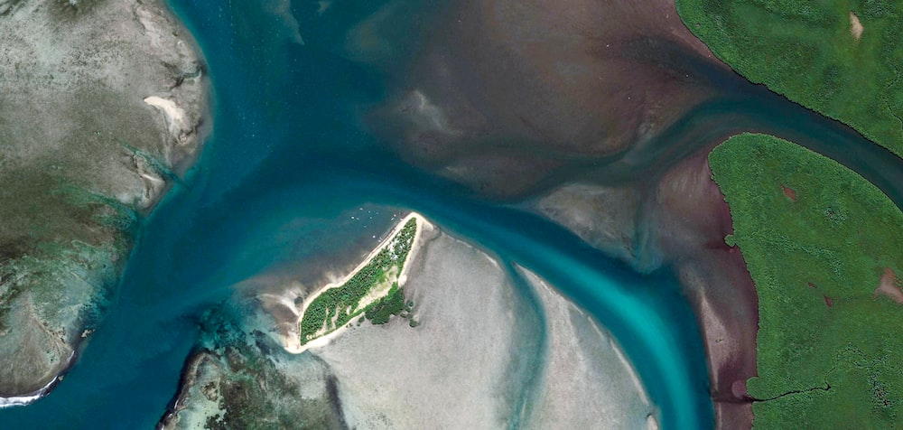 aerial view of green island in the middle of the sea