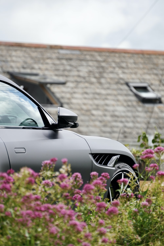 black car parked beside brown brick wall