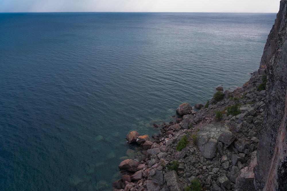 brown rocks beside body of water during daytime