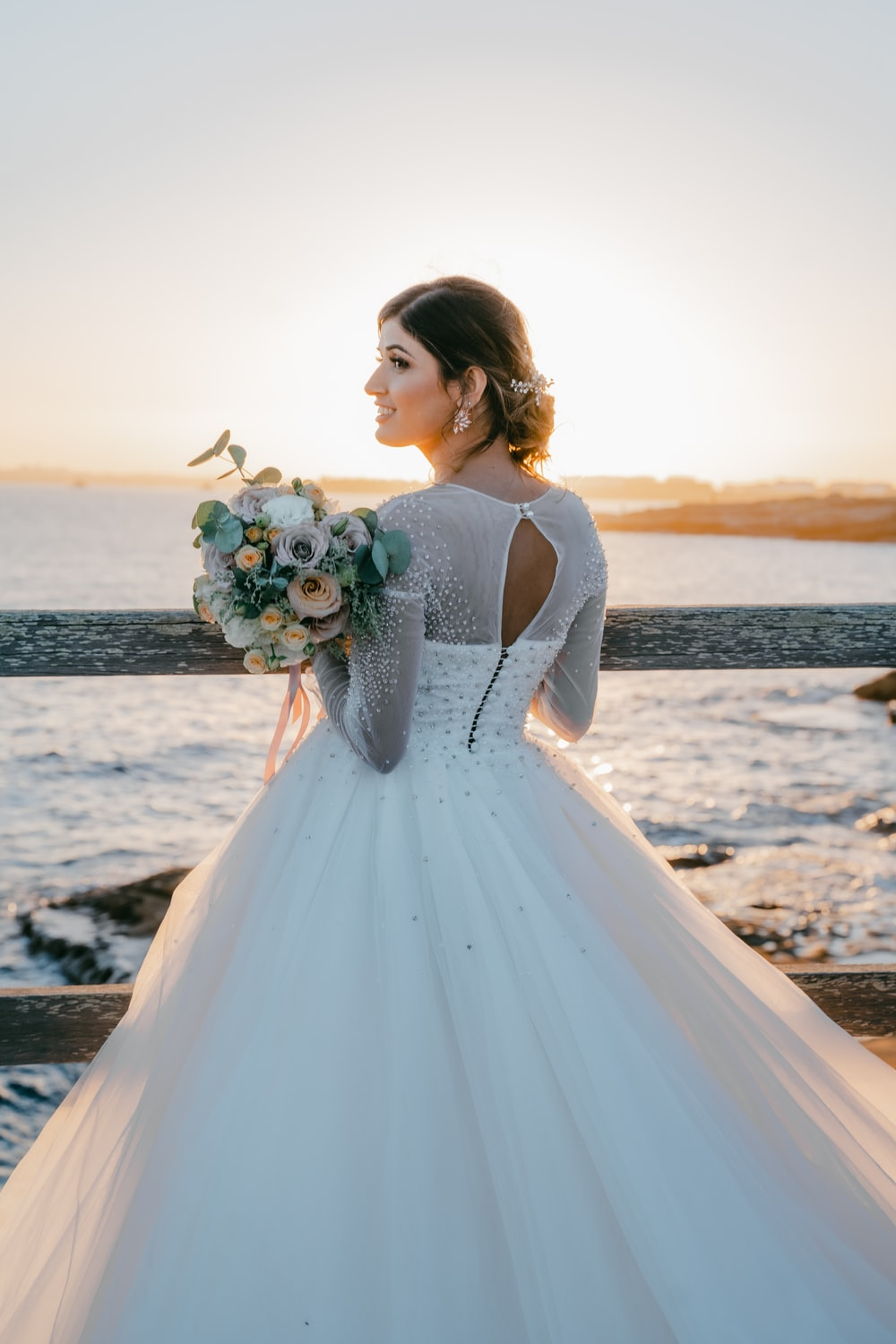 woman in white sleeveless dress holding bouquet of flowers standing on beach during sunset