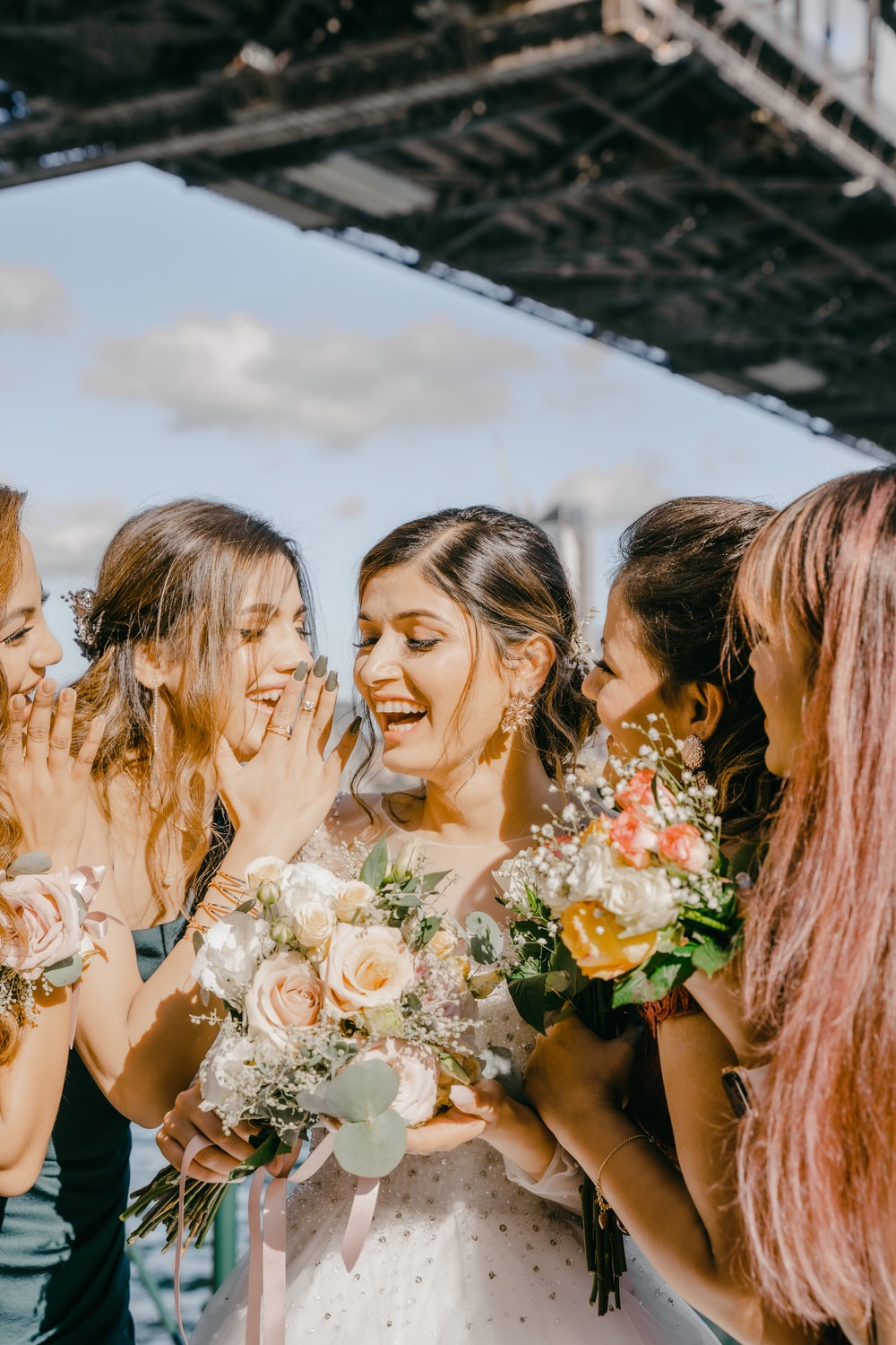 3 women in white floral dress holding bouquet of flowers