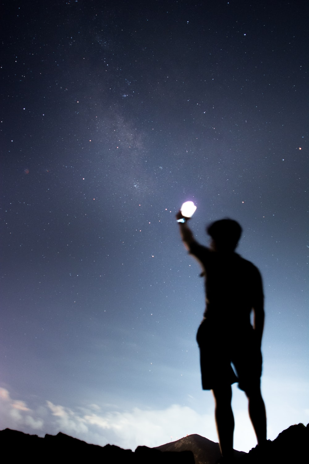 silhouette of man holding lighted light during night time