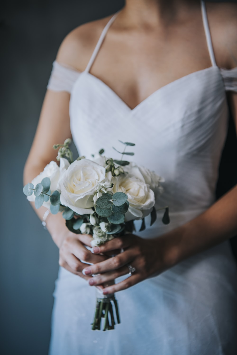 woman in white sleeveless dress holding white rose bouquet