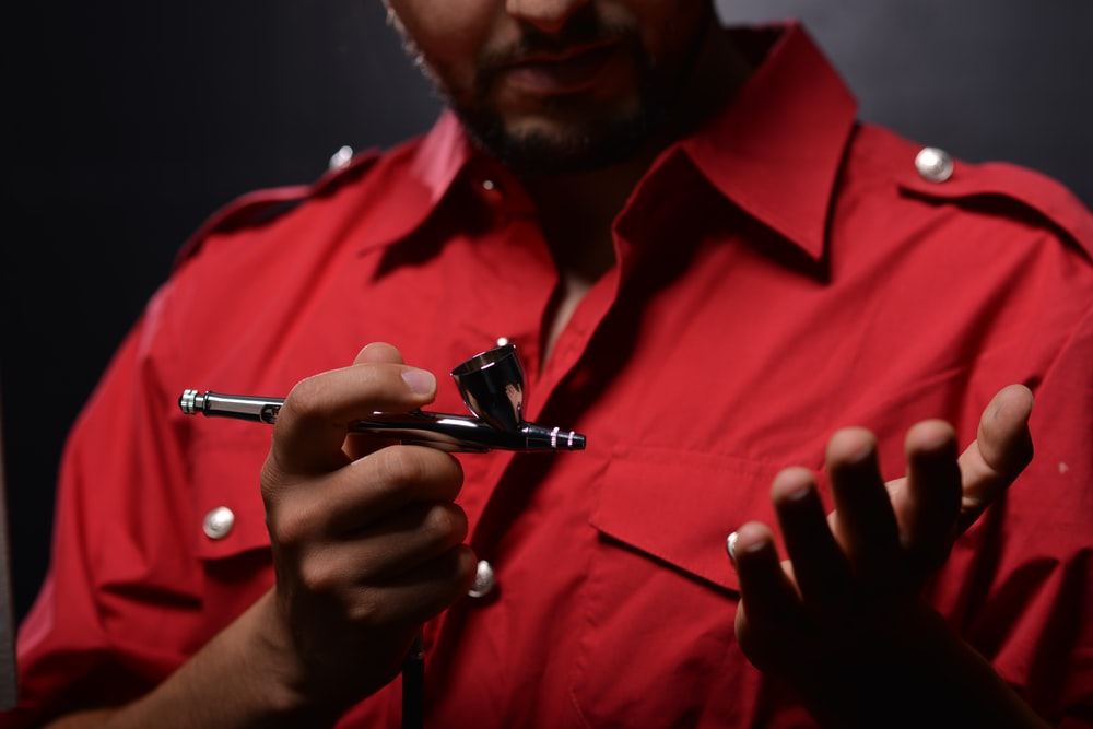 man in red button up shirt holding black pen