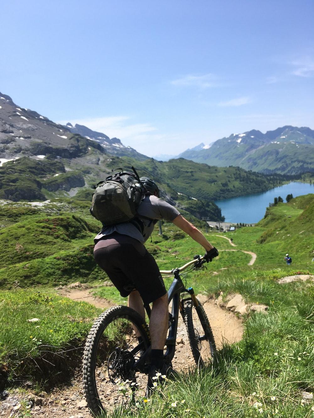 man in black t-shirt riding black mountain bike on green grass field during daytime