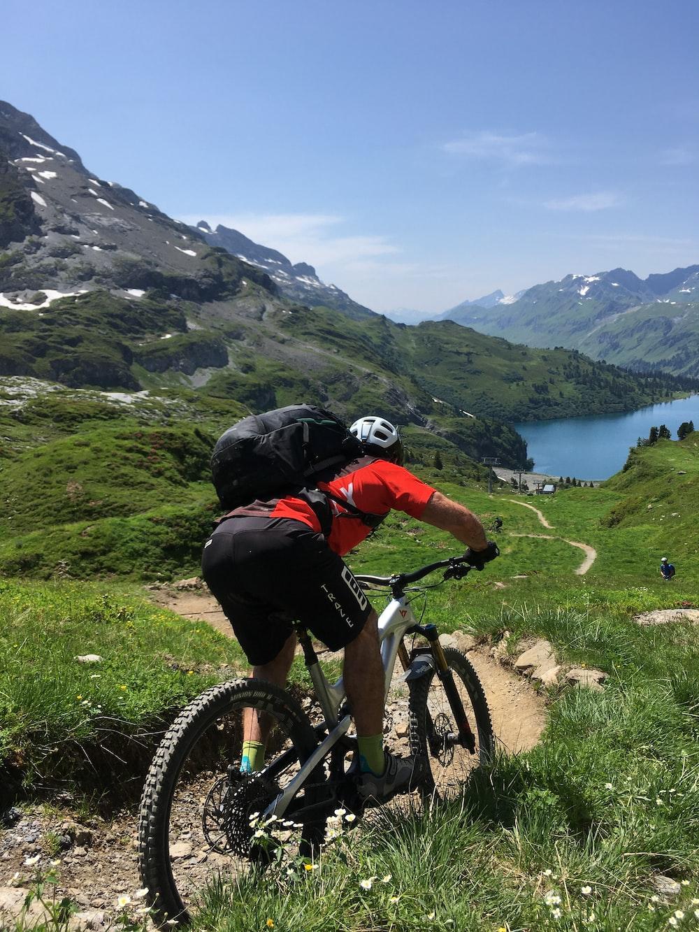 man in black jacket riding on mountain bike during daytime