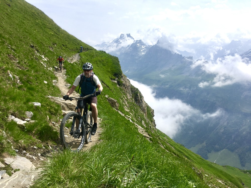 man in black jacket riding mountain bike on green grass field during daytime