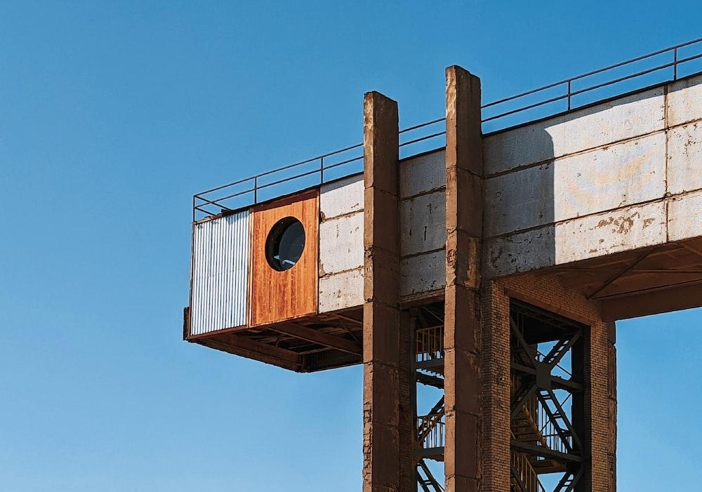 brown wooden birdhouse on brown metal tower