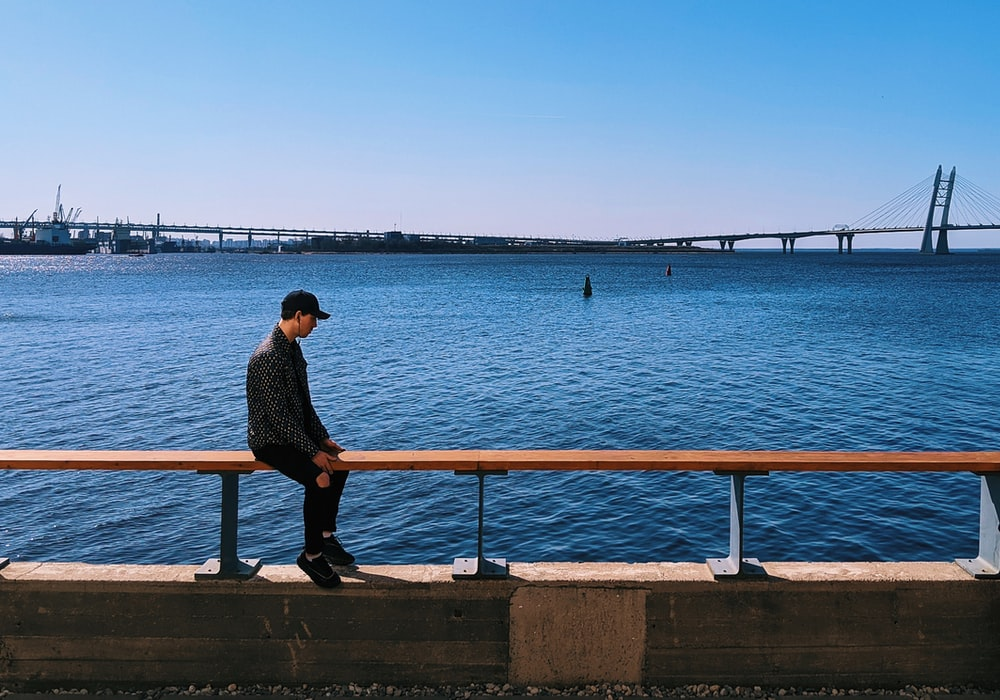 man in black shirt sitting on concrete bench near body of water during daytime
