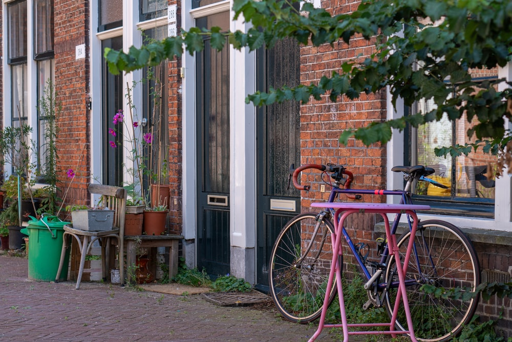 red city bike parked beside green and brown concrete building during daytime