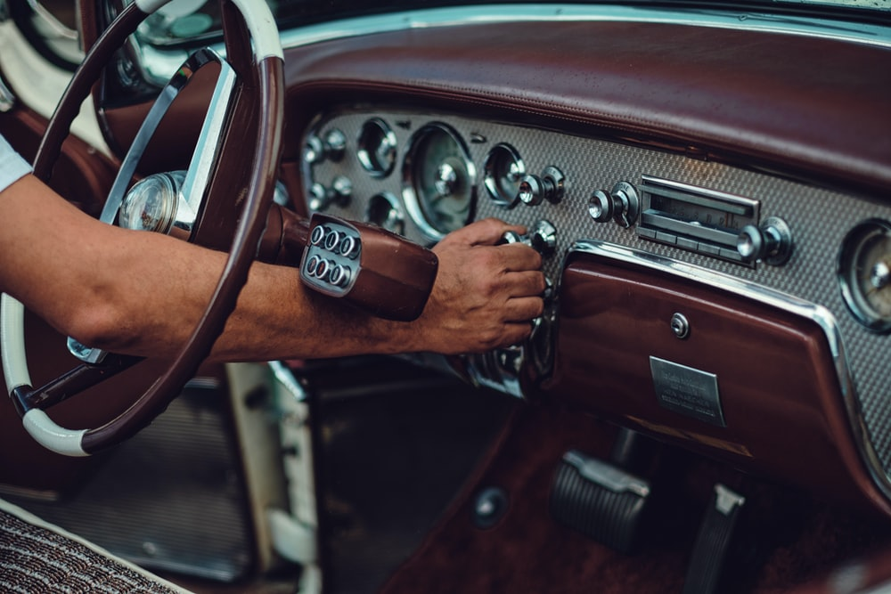person holding car steering wheel
