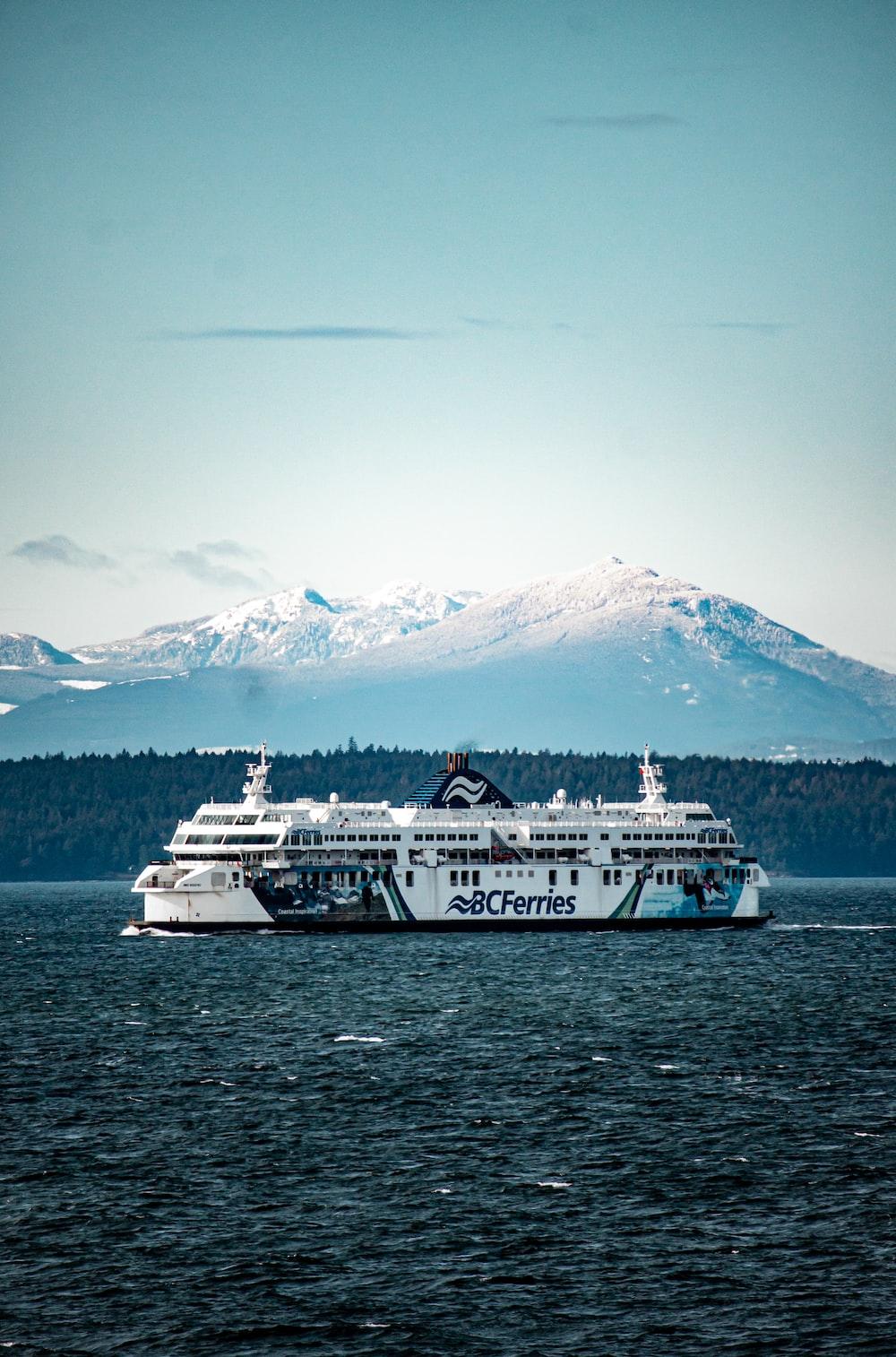 white ship on sea near snow covered mountain during daytime