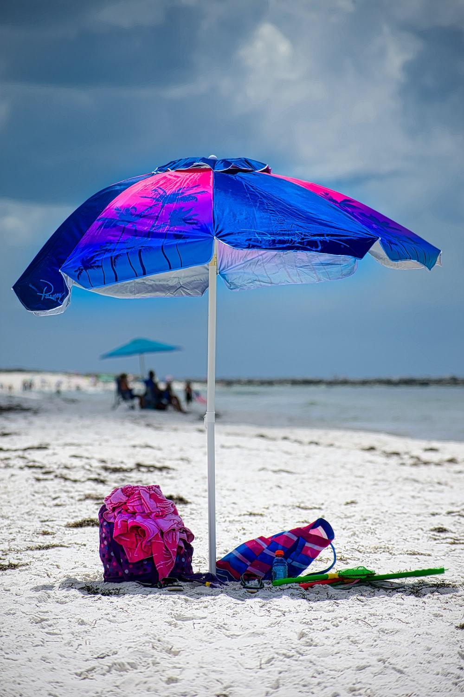 blue umbrella on beach during daytime