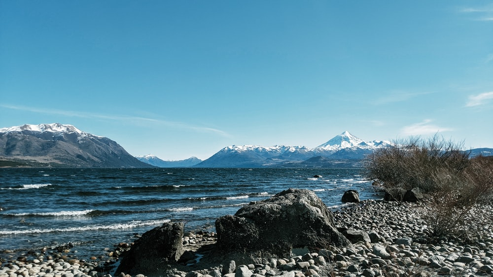 rocky shore with mountain in distance under blue sky during daytime
