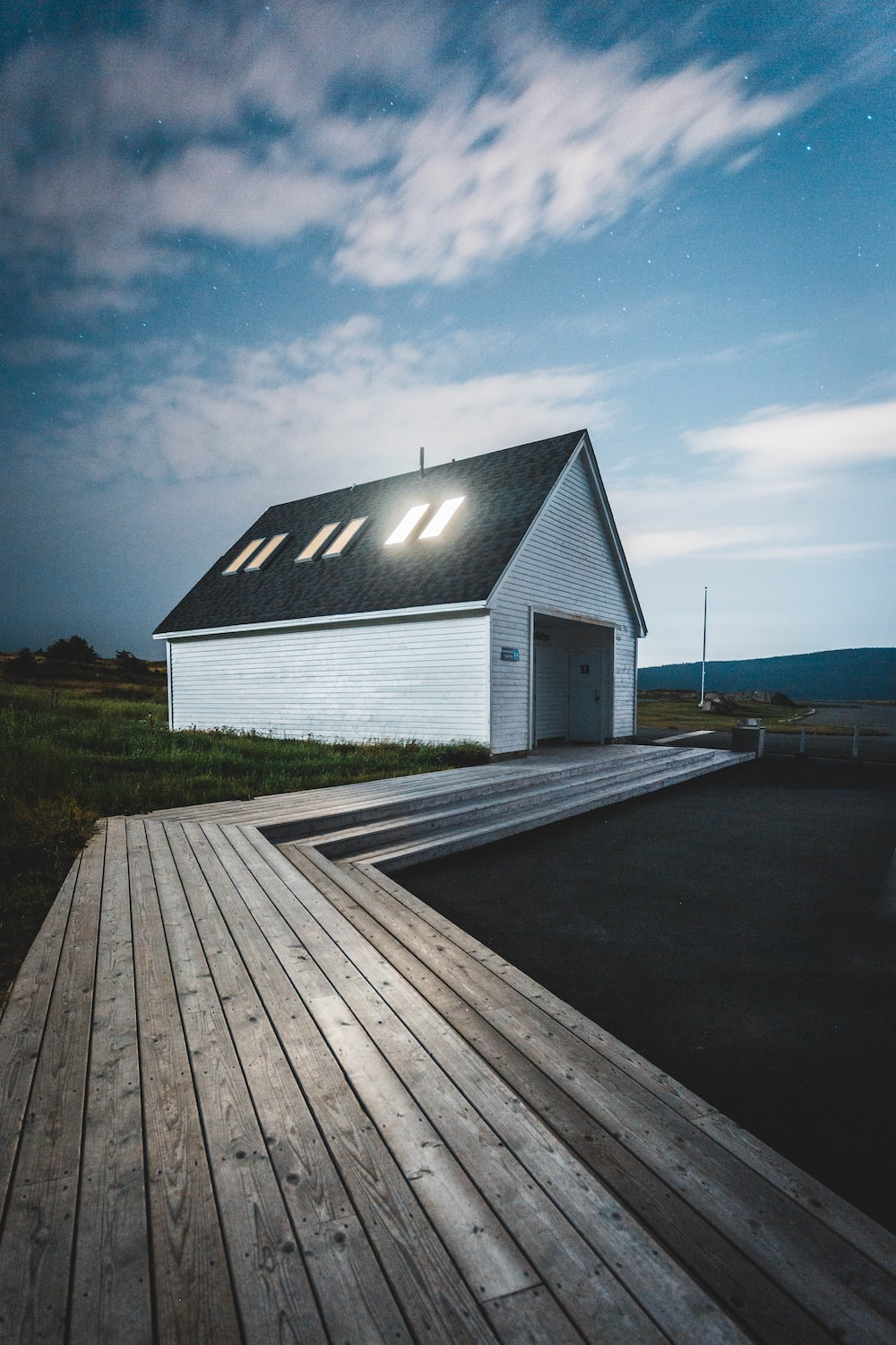 white and black wooden house near green grass field under blue sky during daytime