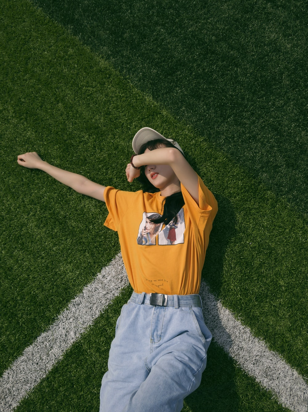boy in orange and black polo shirt lying on green grass field during daytime