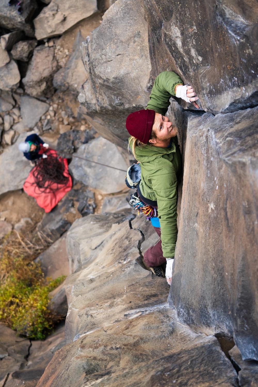 man in green jacket climbing on brown rock during daytime