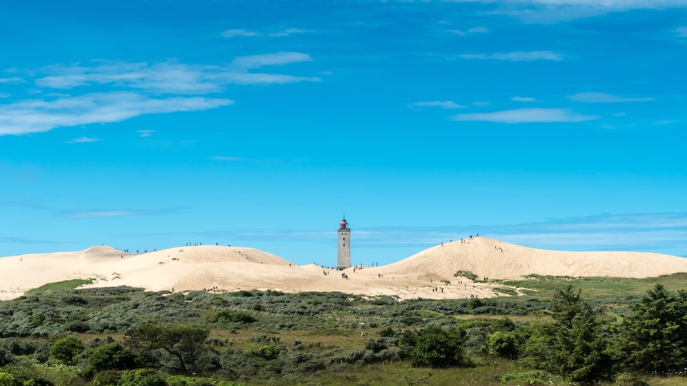 white lighthouse on brown sand under blue sky during daytime