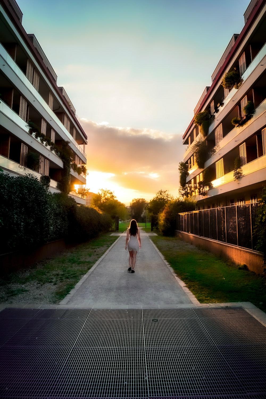 woman in white dress walking on pathway between buildings during daytime