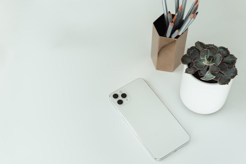 silver iphone 6 on white ceramic mug