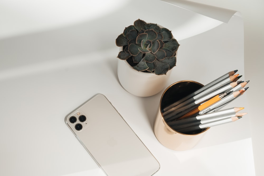 space gray iphone 6 beside white ceramic vase
