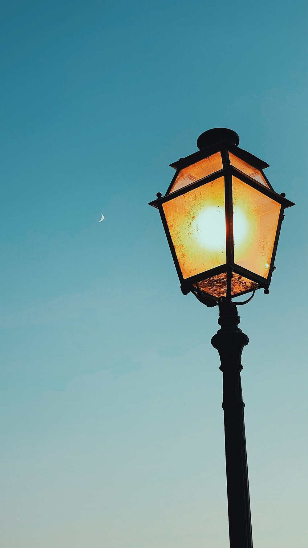 black street lamp turned on during night time