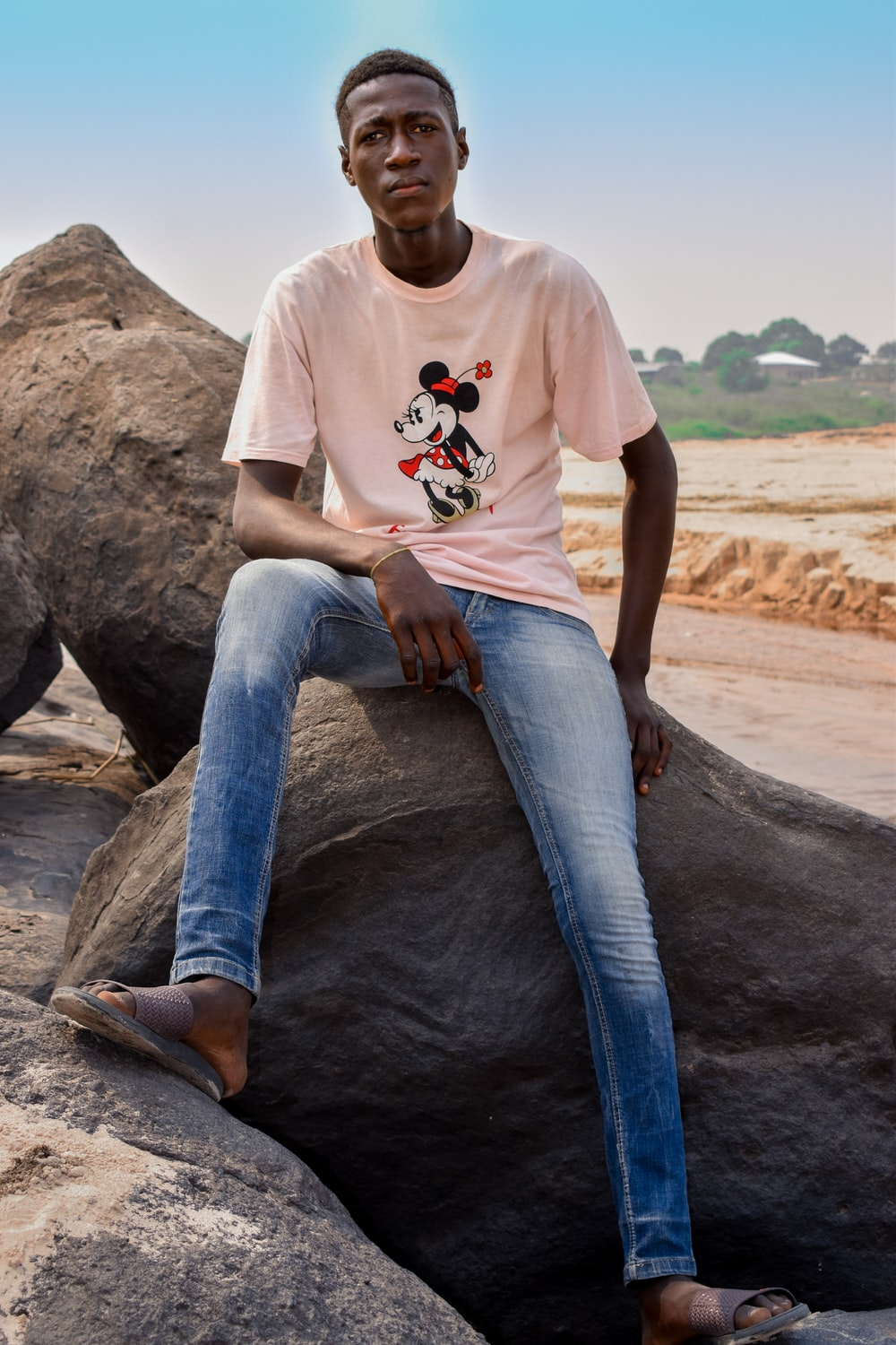 man in white crew neck t-shirt and blue denim jeans sitting on brown rock during